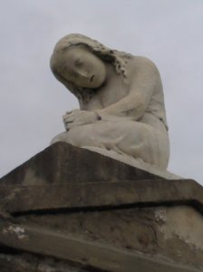 A weather-worn figure of a mourning girl on a tomb in New Orleans.