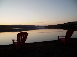 two empty chairs lakeside at sunset