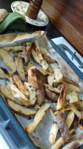 Oven-baked fries cooling on the baking sheet.